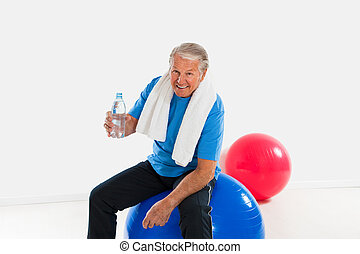 active seniors - senior man sitting on fitness ball in gym...