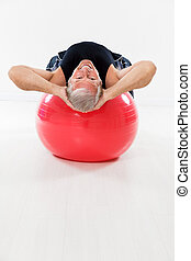 active seniors - senior man working out on fitness ball and...