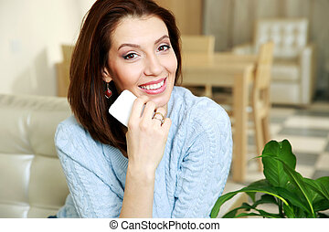 Smiling woman sitting on the sofa and holding smartphone at...