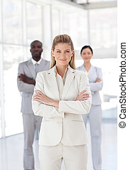 Business woman with folded arms in front of associates