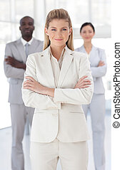 Business woman with folded arms in front of associates -...