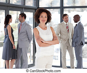 Business woman with Folded arms in Front of Business team...