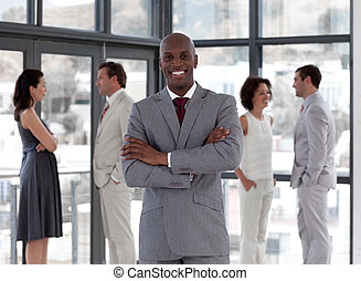 Potrait of a Business man standing smiling in front of team