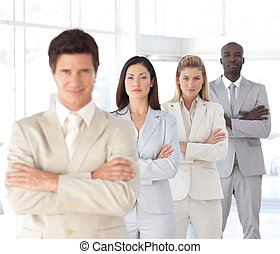 Business man with arms folded in front of Business Team -...