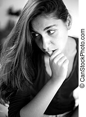 Black and white portrait of young woman thinking