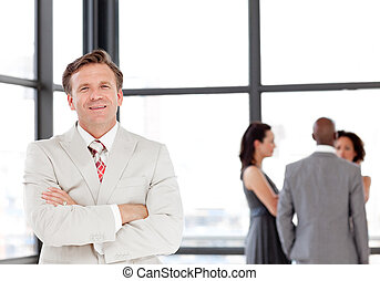 Senior Business Man with arms folded in Front of team -...