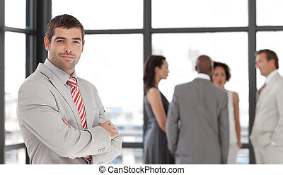Senior Business Man with arms folded in Front of team