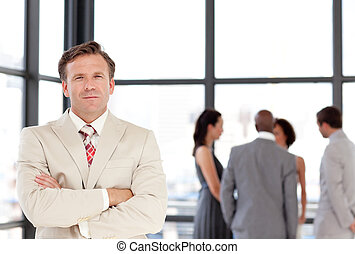 Senior Businessman standing in Front of Business team