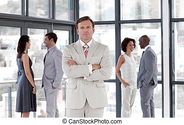 Senior Business man standing in from of Business team -...
