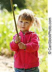 beautiful little girl in nature playing with a stick - a...