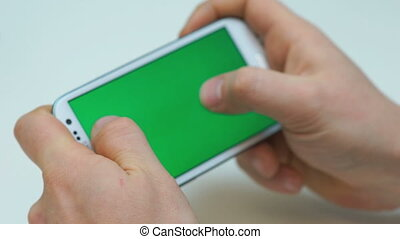Two hands holding white smart phone, playing games, - Two...