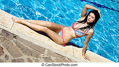 Perfect body of female model posing in front of swimming...