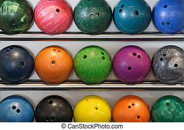 Bowling balls - A rack of old worn bowling balls