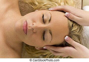 Relaxing Head Massage - A young blond woman receiving a...