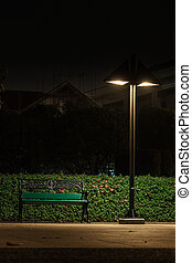 Bench under a lamp In the park alone at night.