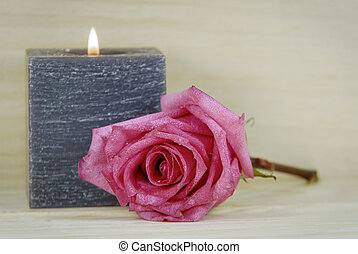 in memoriam - a rose and a grey candle in the background