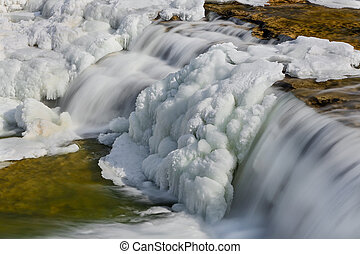 Frosty Falling Water - Water flows over a partially frozen...