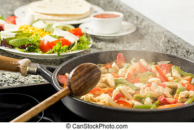 Pan cooking vegetables and chicken in the kitchen