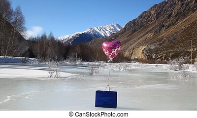 Blue gift package and the helium balloon is on the ice in...