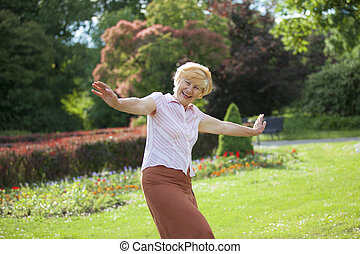 Gaiety. Delighted Playful Mature Woman with Outstretched...