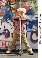 Cute little girl with scooter near graffiti painted wall -...