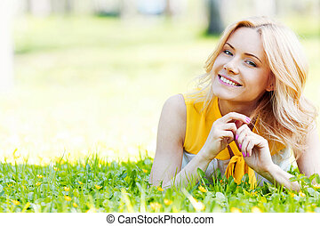 Woman on grass - Blonde woman laying on the grass and...