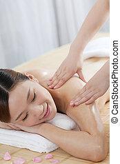 A young woman enjoying massage at spa salon