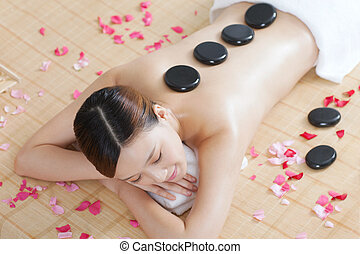 A young lady enjoying stone massage at spa salon, indoors...