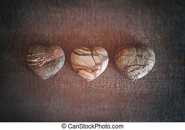 Three stone hearts on wood background