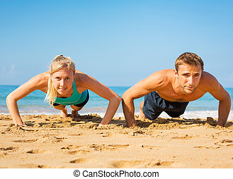 Couple doing push ups on the beac - Athletic couple doing...