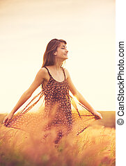 Romantic Model in Sun Dress in Golden Field at Sunset -...