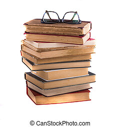 Stack of old antique books and spectacles, isolated on white...