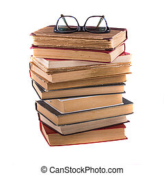 Stack of old antique books and spectacles in thick-rimmed, isolated on white background.