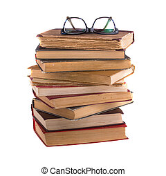 Stack of old books and spectacles in thick-rimmed, isolated on white background.