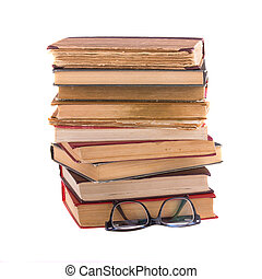 Stack of old books and spectacles, isolated on white background.