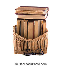 Stack of old antique books in a wicker basket and spectacles...