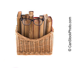 Stack of old books in a wicker basket and spectacles in thick-rimmed, isolated on white background.
