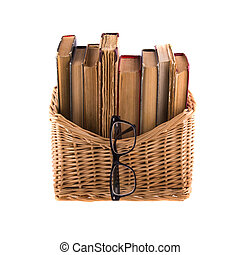 Stack of old antique books in a wicker basket and spectacles in thick-rimmed, isolated on white background.