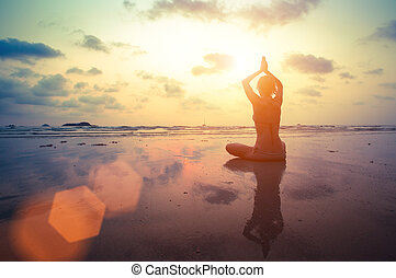 Silhouette young woman practicing yoga on the beach at surrealistic sunset.