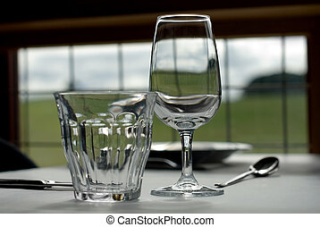 Glasses - A water glass, and a wine glass, on a table in a...