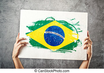 Brazil flag. Man holding banner with Brazilian Flag....