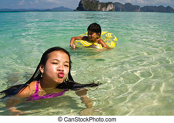 Two girls in the water at the beach of the Koh Ngai island...