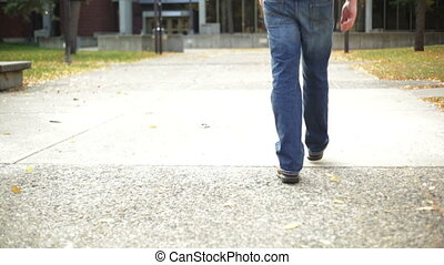 Student walking on college campus - College student walking...