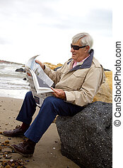 Happy elder man reading newspaper on the beach - Relaxing on...