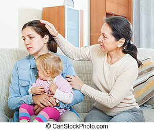 Mature woman comforting adult daughter with baby