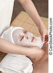 Facial mask for the young lady at spa salon, indoors Photo...