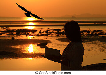 Silhouette woman reading book by beach at sunrise