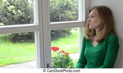 sad woman window sill - sad worried crouched woman sits on...