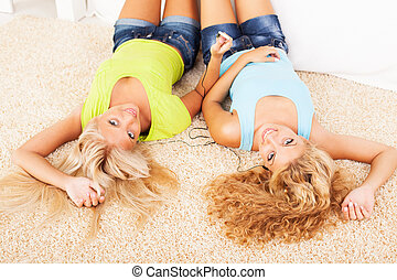 Leisure time - Two Beautiful girls lying in the carpet and...