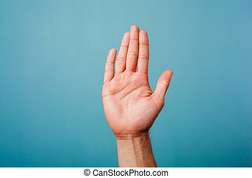 Hand raised against a blue background